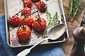 Roasted vine tomatoes with thyme on a baking tray