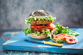 A veggie burger with tomatoes and lettuce