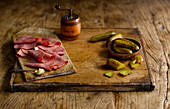Pastrami and gherkins on a wooden cutting board