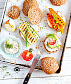 Sesame seed wholemeal rolls with vegetarian toppings