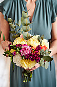 A woman holding a birthday bouquet with carnations and eucalyptus