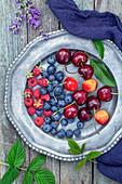 Beeren und Kirschen auf Vintage-Metallteller