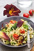 Bandnudeln mit Brokkoli, Tomaten und Taglilienblüten