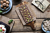 Tasty chocolate dessert garnished with pistachios on baking paper