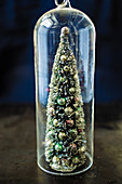 A decorative Christmas tree under a glass cloche