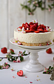 A cheesecake with a biscuit base and strawberries
