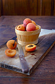An arrangement of apricots in a wooden basket with a halved apricot next to it