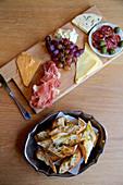 Käse, Schinken, Wurst und Trauben auf Holzbrett dazu Baguettebrot