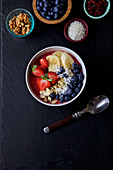 Pitaya bowl with bananas, blueberries almonds, strawberries, coconuts flakes and cranberries
