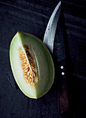 Galia melon wedge on a black stone surface with a rustic knife