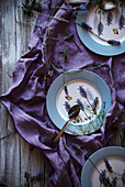 From above fresh lavenders placed around empty plates over violet fabric on lumber tabletop