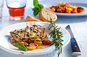 Grilled marinated pork loin steak with roasted tomatoes and baguette