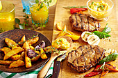 Spicy grilled pork collar steaks with potato wedges, grilled vegetables and a mango and tomato salsa