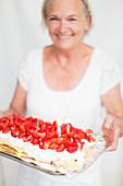 Lachende Frau mit Erdbeerkuchen
