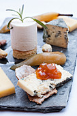 A cheese plate with mustard jam, poached pear and crackers