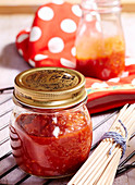 Homemade fruity barbecue sauce in a jar for grilled food