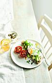 Brot mit Avocadopüree, pochiertem Ei und gegrillten Tomaten