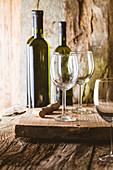 Rustikales Stilleben mit Weißweinflaschen und Gläsern