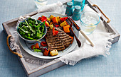 Grilled rump steak with roast vegetables and salad