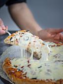 Pizza with prosciutto, mozzarella and vegetables