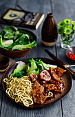 Szechuan style pork with noodles and pak choi
