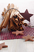 Cinnamon sticks and wooden stars on a purple surface
