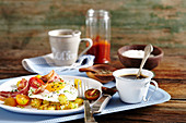 Fried potatoes, bacon, fried egg and tomatoes and breakfast with coffee