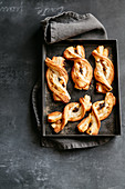 Puff pastry candies with candied fruit, chocolate and macadamia