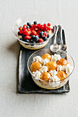 Layered dessert topped with vanilla cream, champagne cream, and caramelised profiteroles, or topped with fresh berries