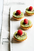 Almond cream cakes with pine nuts, kiwi and raspberries