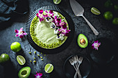 Avocado-Limetten-Cheesecake dekoriert mit Blüten und Pistazien