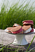 A cake stand with vanilla and raspberry ice cream sandwiches