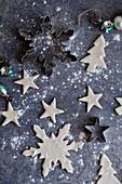 Ungebackene Weihnachtsplätzchen in verschiedenen Formen und Ausstecher