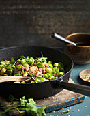 Brussels sprouts with bacon on frying pan