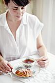 Frau am Tisch mit Tasse schwarzem Tee und Plunderteilchen