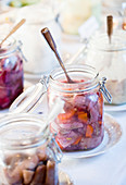 Herring salad with carrots in glass jars at a buffet
