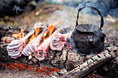 Kettle and animal bones on campfire