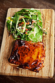 Meat pie and salad on a wooden board (England)