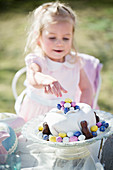 Girl reaching for Easter cake with sugar eggs