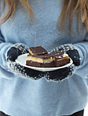 A woman wearing gloves holding a plate of chocolate semolina cake