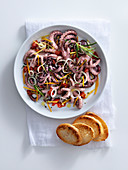Warm octopus salad with rosemary, lemon, cherry tomatoes and onions