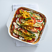 Zucchini bake with mozzarella, tomatoes and zucchini flowers