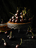 Still life with cherries on a decorative wooden stand