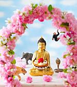 Buddha mit Himbeertörtchen und Blumendeko