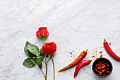 A symbolic image for spicy romantic meals: roses and chilli