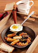 Scottish breakfast with baked beans, black pudding, bratwurst and a fried egg