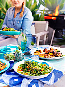 A table set with summer salad and a grill plate