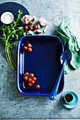 A blue baking dish with cherry tomatoes