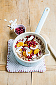 Coconut and clementine porridge with flax seeds and pomegranate seeds