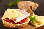 A sandwich with homemade tomato relish, ham and Emmental